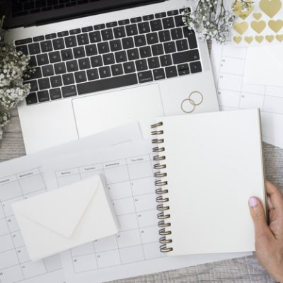 close-up-person-holding-blank-spiral-notebook-with-laptop-wedding-rings-flower-envelope-calendars-wooden-desk_23-2147936626